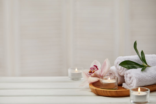 Spa composition with aromatic candles, orchid flower and towel on white wooden table. Beauty spa treatment. copy space