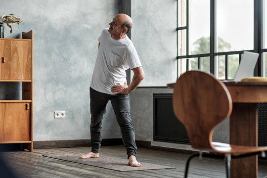 Elderly man practicing yoga or fitness during trikonasana.