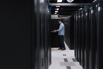 Server room technician using computer in server room