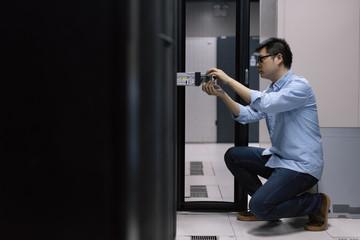 Server room technician inserting hard disk into server