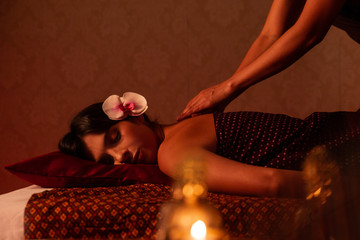 Anonymous thai female massagist giving a massage to a young woman