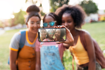 Three african girls taking photo self portrait on a smartphone i