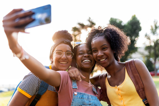 Three smiling girl friends making selfie with smart phone.