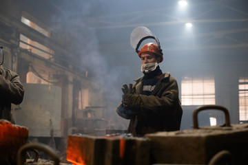 Foundry worker putting on gloves in workshop