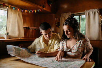 Couple reading map in camper
