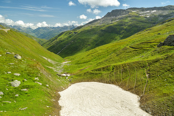 Wall Mural - Remnants of old snow on top of Furka high mountain pass in Swiss Alps