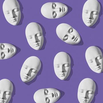 White plaster masks in pattern layout