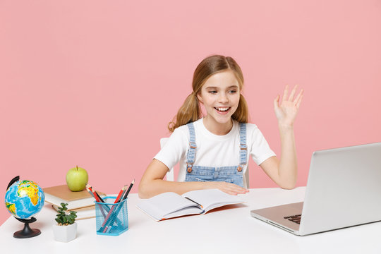 Funny little kid schoolgirl 12-13 years old sit study at desk isolated on pink background. School distance education at home during quarantine concept. Waving greeting with hand to laptop pc computer.