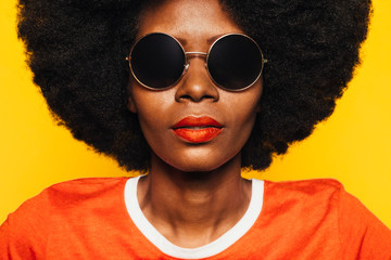 Beautiful Afro Woman posing over yellow background with round sunglasses