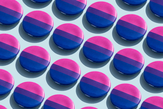 Close up of bisexual pride flag badges on table