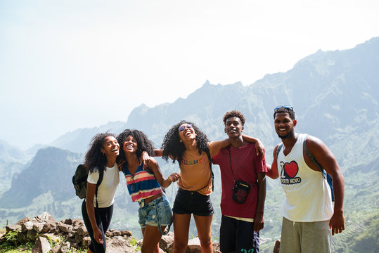 group of black ethnic friends embracing each other and enjoying