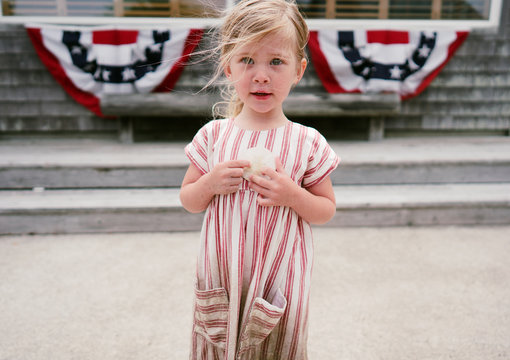 little girl in red striped dress on fourth of july in america holds seashell covered in sand from the beach with american flags in the background