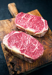 Deurstickers Steakhouse Raw dry aged wagyu entrecote beef steak roast as closeup on a rustic wooden cutting board
