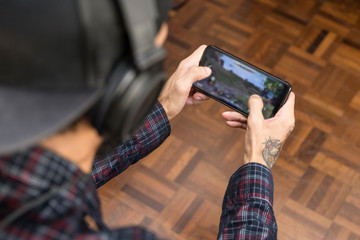 Close up of a man hand paying a mobile game at home. Smart phone, blurred screen
