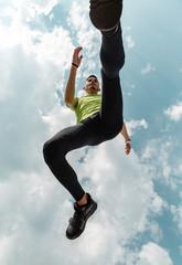 From below of jumping sportsman under blue sky