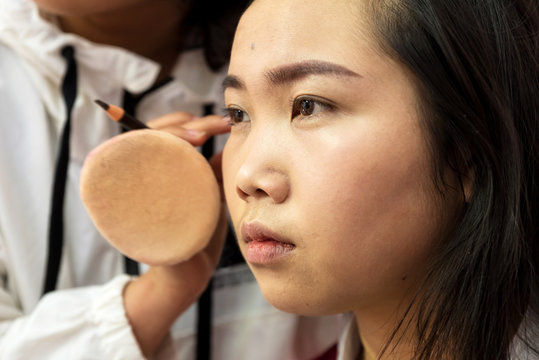 Make up artist applying make up to a Chinese woman