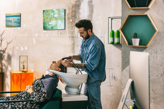 Hairstylist Washing Hair of Female Customer in Shabby Chic Studio