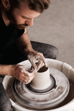 Potter throwing new shape on a wheel
