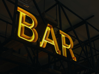 Glowing bar sign on metal construction