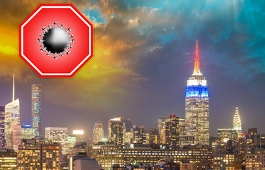 Wall Mural - New York City, USA. Concept image with large red coronavirus warning sign in front of Manhattan skyline at night, travel restriction concept, covid-19 virus outbreak