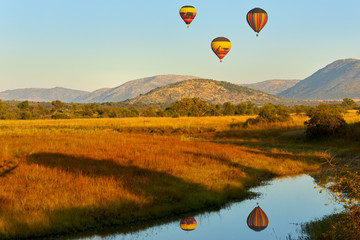 Poster de jardin Montgolfière / Dirigeable Hot air balloons with tourists above the Pilanesberg reserve. Three hot air balloons, decorated safari motifs against blue sky, mountains on background. Holiday Safari in South Africa.