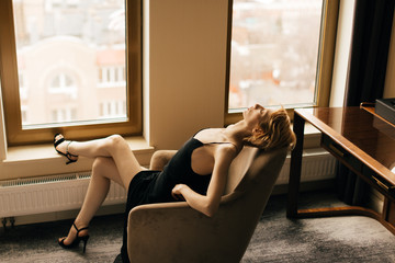 Portrait of tired blonde woman in the arm-chair Fotobehang