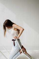 Stylish woman crawling with chair