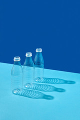 Plastic bottles on a double blue background with reflection of shadows