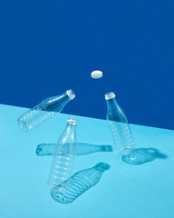 Plastic cap and bottles in the air on a double blue background