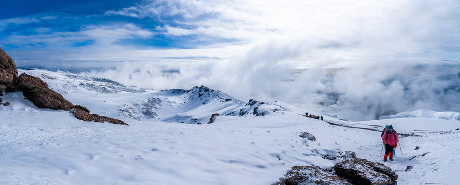 Group of trekkers hiking among snows and rocks of Kilimanjaro mountain