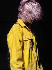 Fashionable portrait of a beautiful girl with pink hair in a yellow shirt