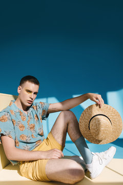 Male model in summer clothes with straw hat