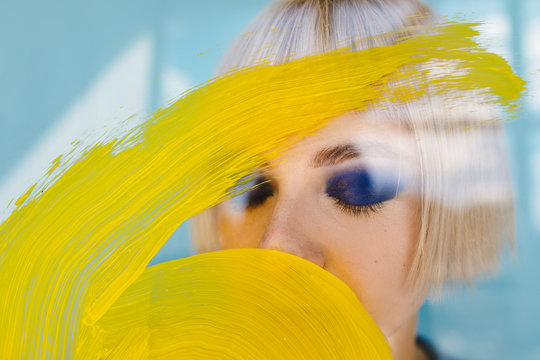 Young model behind glass with yellow paint