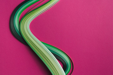 Multi colored quilling paper lying on colorful paper