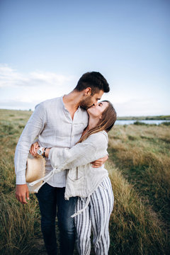 Happy couple in love hugging, kissing and smiling against the sky in field. Hat in girl's hand
