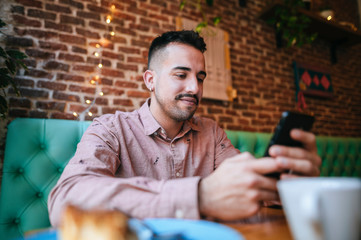 Portrait of a smiling man in a cafe looking at cell phone Wall mural