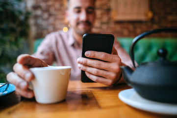 Close-up of man in a cafe with tea cup and cell phone Wall mural
