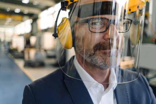 Portrait of a businessman wearing safety helmet and earmuffs in a factory