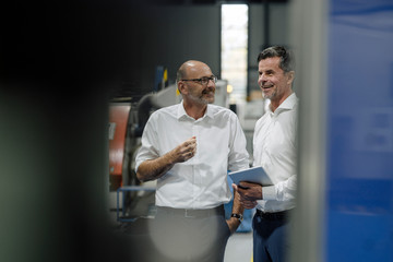 Two smiling businessmen talking in a factory