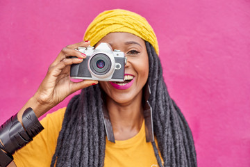 Portrait of woman with long dreadlocks and retro style camera in front of a pink wall