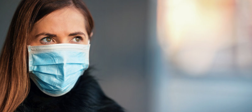 Young woman wearing disposable blue virus face mouth nose mask, closeup portrait, banner with space for text right side. Coronavirus covid-19 outbreak prevention concept