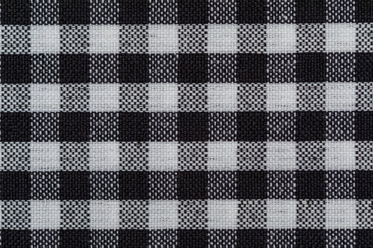 Checkered fabric background. Black cell. Top view, flat lay