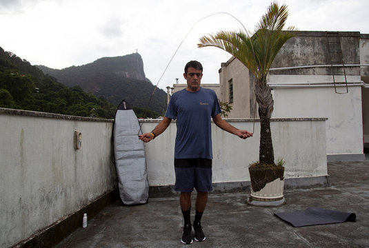 Surfer Bruno Bocayuva exercises on the rooftop of his apartment complex, amid the coronavirus disease (COVID-19) outbreak, in Rio de Janeiro