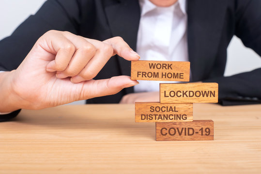 business hand building corona virus covid-19 concept with wooden blocks on wood, covid-19, Social distancing, lockdown, work from home.