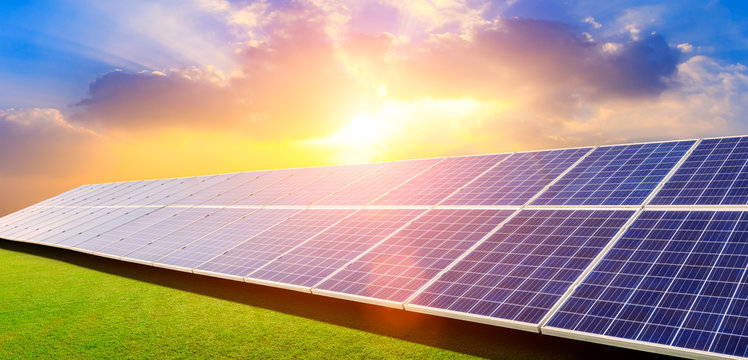 Photovoltaic solar panels and green grass on sky background,green clean alternative energy concept.