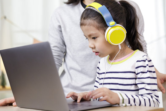 Asian little child girl learning at home with laptop computer using meeting online app with her mother, Quarantine isolation during the Coronavirus (COVID-19) health care, online education concept
