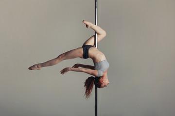 Fototapeta Beautiful sports girl doing acrobatics on a pole obraz