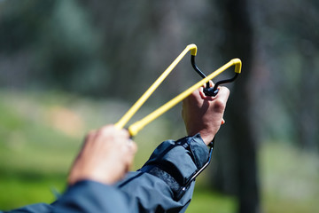 Slingshot aimed and pulled back against wrist, with hands - in forest setting