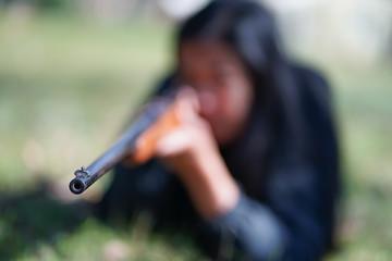 Focus on Gun Barrel, With Woman Shooter Bokeh