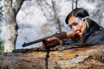 Huntress Shooting Rifle in Woods, With Safety Goggles On